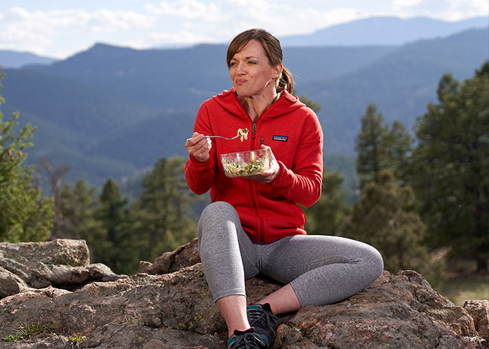 Woman in red jacket eating from a glass bowl on too=p of a mountain